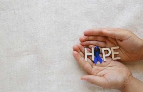 HOPE with Blue ribbon on hands, Colon Cancer, Colorectal Cancer, Child Abuse awareness