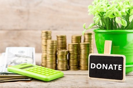 """Stacks of coins and dollar bills, calculator, blackboard with text """"DONATE"""" on wooden background. Business and Financial concept"""